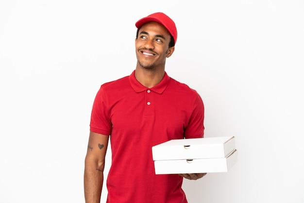 Afro-amerikaanse pizzabezorger die pizzadozen ophaalt over een geïsoleerde witte muur en een idee denkt terwijl hij omhoog kijkt
