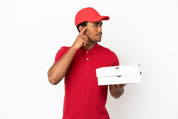 Afro-amerikaanse pizzabezorger die pizzadozen ophaalt over een geïsoleerde witte muur en een idee denkt