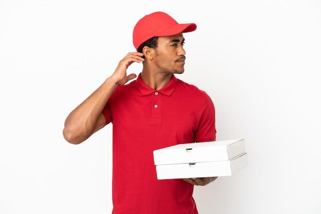 Afro-amerikaanse pizzabezorger die pizzadozen ophaalt over een geïsoleerde witte muur met twijfels