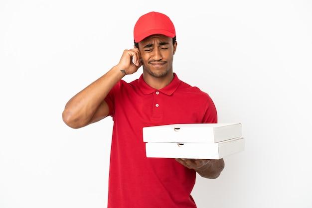 Afro-amerikaanse pizzabezorger die pizzadozen ophaalt over geïsoleerde witte muur gefrustreerd en oren bedekt