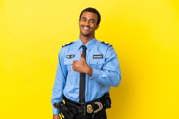 Afro-amerikaanse politieman over geïsoleerde gele achtergrond die een duim omhoog gebaar geeft