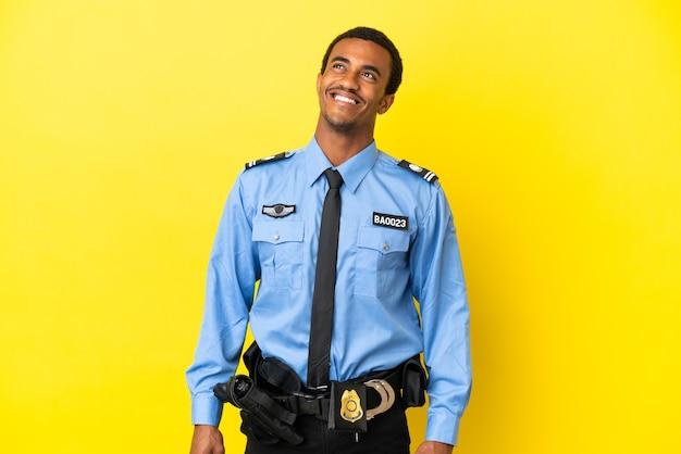 Afro-amerikaanse politieman over geïsoleerde gele achtergrond die een idee denkt terwijl hij omhoog kijkt