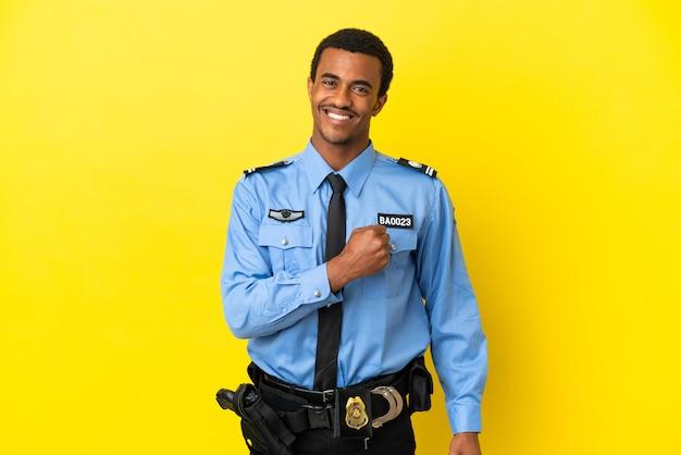 Afro-amerikaanse politieman over geïsoleerde gele achtergrond die een overwinning viert