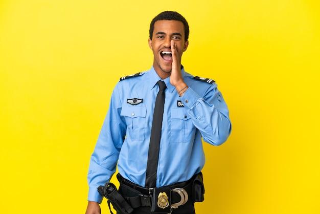 Afro-amerikaanse politieman over geïsoleerde gele achtergrond die met wijd open mond schreeuwt