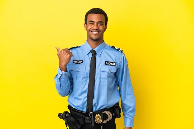 Afro-amerikaanse politieman over geïsoleerde gele achtergrond die naar de zijkant wijst om een product te presenteren