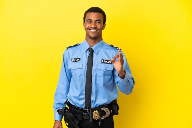 Afro-amerikaanse politieman over geïsoleerde gele achtergrond die ok teken met vingers toont