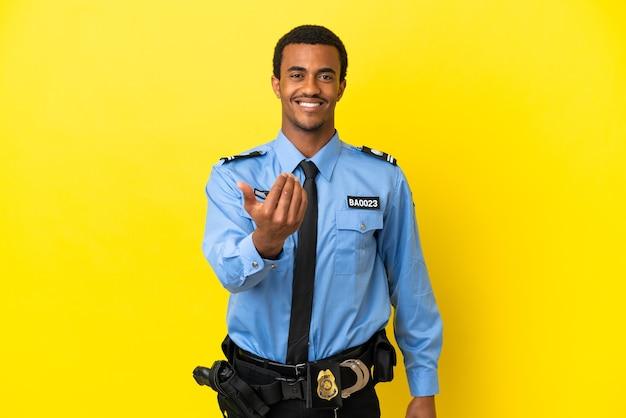 Afro-amerikaanse politieman over geïsoleerde gele achtergrond die uitnodigt om met de hand te komen. blij dat je gekomen bent