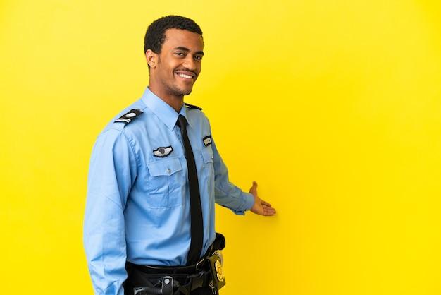 Afro-amerikaanse politieman over geïsoleerde gele achtergrond die zijn handen naar de zijkant uitstrekt om uit te nodigen om te komen