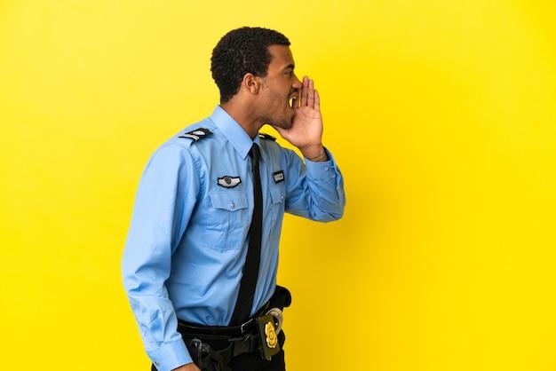 Afro-amerikaanse politieman over geïsoleerde gele achtergrond schreeuwend met mond wijd open naar de zijkant