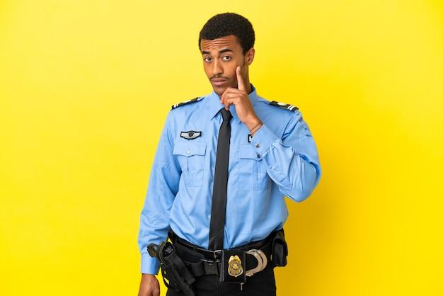 Afro-amerikaanse politieman over geïsoleerde gele muur die een idee denkt