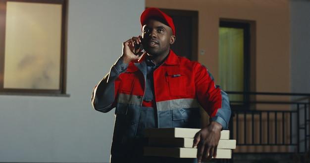 Afro-amerikaanse postbode in het blauwe kostuum en pet met karton percel spreken op de mobiele telefoon 's nachts. buitenshuis.