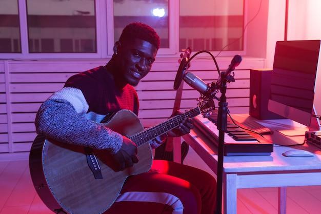 Afro-amerikaanse professionele muzikant gitaar opnemen in digitale studio thuis, muziekproductie