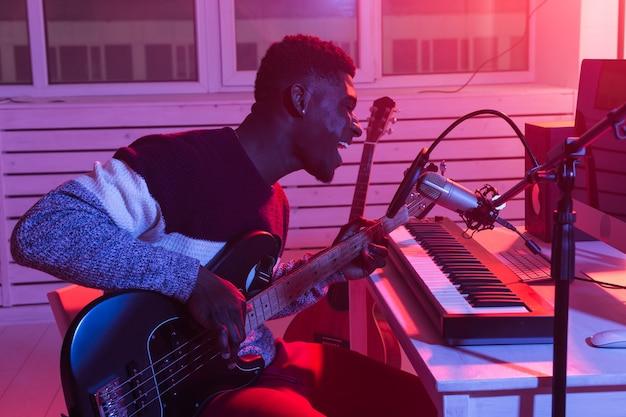 Afro-amerikaanse professionele muzikant opname basgitaar in digitale studio thuis, muziek