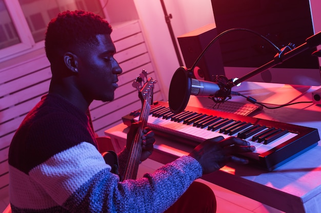Afro-amerikaanse professionele muzikant opname synthesizer in digitale studio thuis, muziek