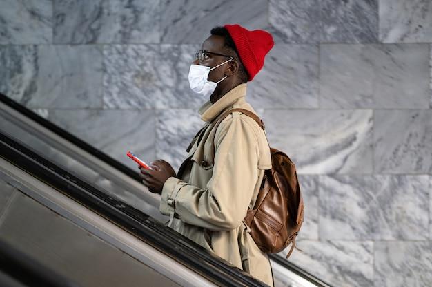 Afro-amerikaanse reiziger man staat op roltrap in metro of treinstation