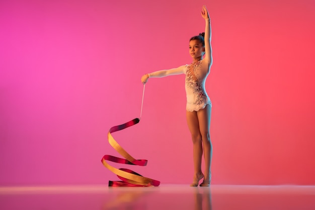 Afro-amerikaanse ritmische turnster mooi meisje oefenen op kleurovergang muur in neonlicht