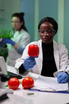 Afro-amerikaanse scheikundige onderzoeker arts analyseert peper geïnjecteerd met pesticiden