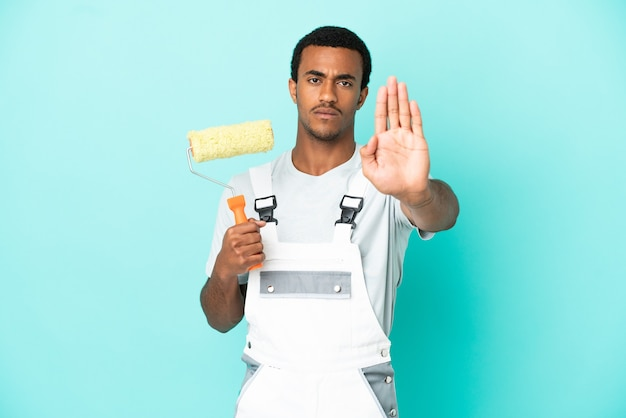 Afro-amerikaanse schilder man over geïsoleerde blauwe achtergrond stop gebaar maken