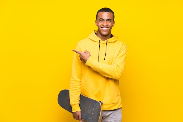 Afro-amerikaanse skater man wijst naar de zijkant om een product te presenteren