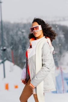 Afro-amerikaanse skiër vrouw in zwembroek met snowboard bril met vrolijke gezichtsuitdrukking