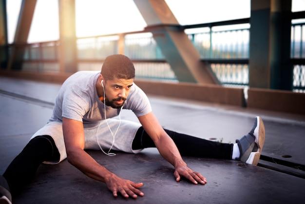 Afro-amerikaanse sportman die zijn lichaam opwarmt voor een buitentraining