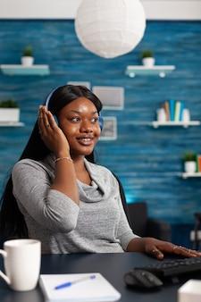 Afro-amerikaanse student die hoofdtelefoon draagt die online leercursus luistert
