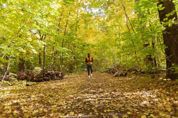 Afro-amerikaanse student die in het herfstseizoen in het park loopt