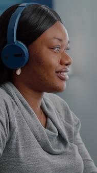 Afro-amerikaanse student die koptelefoon op het hoofd zet, begin ontspannende muziek te luisteren