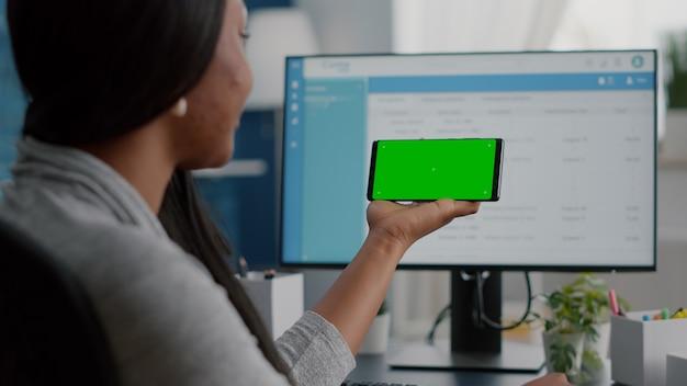 Afro-amerikaanse student die op afstand van huis werkt en kijkt met een mock-up groen scherm