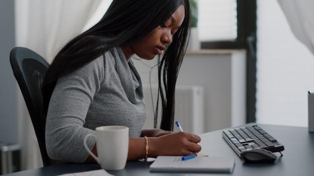Afro-amerikaanse student die universiteitsinformatie schrijft op plaknotities die op de computer worden gezet