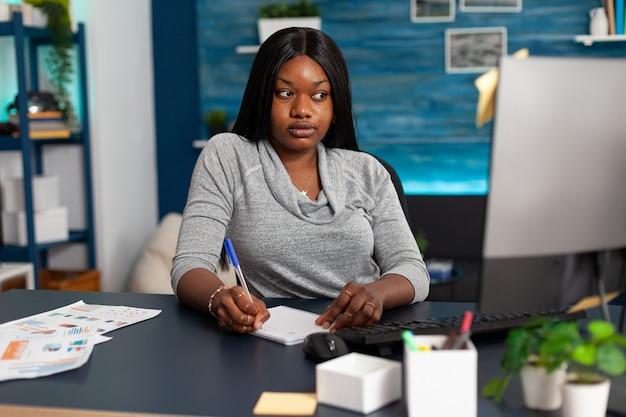 Afro-amerikaanse student kijkt naar communicatiecursus op computer