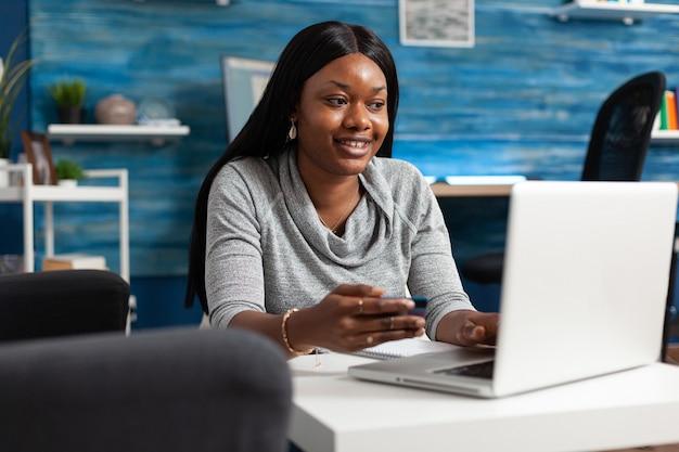 Afro-amerikaanse student maakt online verkoop winkelen met economie creditcard in handen