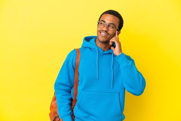 Afro-amerikaanse student man over geïsoleerde gele achtergrond die een idee denkt terwijl hij omhoog kijkt