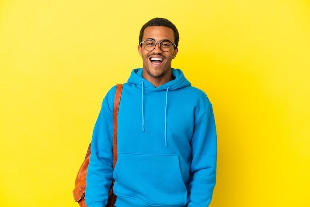 Afro-amerikaanse student man over geïsoleerde gele achtergrond met verrassing gezichtsuitdrukking