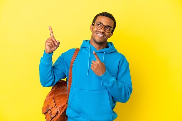 Afro-amerikaanse student man over geïsoleerde gele achtergrond wijzend met de wijsvinger een geweldig idee