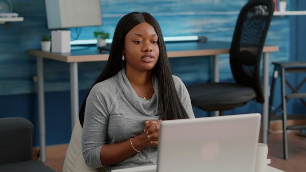 Afro-amerikaanse student met donkere huid zwaaiend schoolteam dat vanuit huis werkt