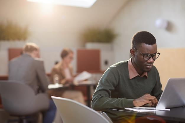 Afro-amerikaanse student werkt in cafe