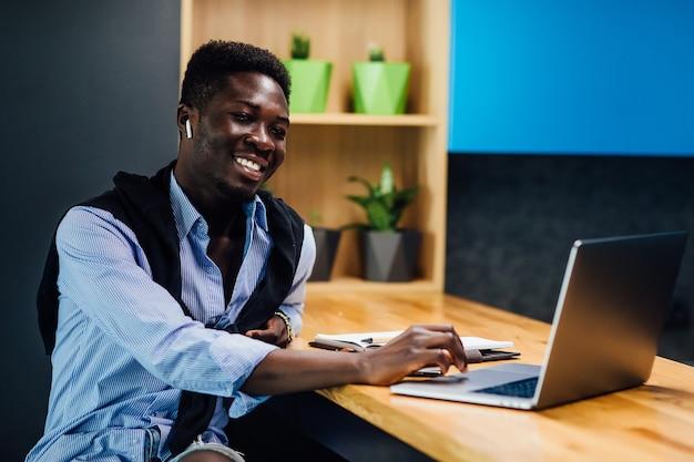 Afro-amerikaanse student werkt vanuit huis met behulp van laptop in de keuken.