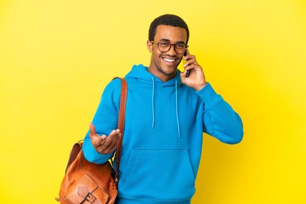 Afro-amerikaanse studentenman over geïsoleerde gele achtergrond die een gesprek voert met de mobiele telefoon met iemand