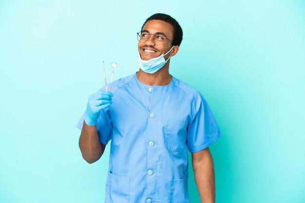 Afro-amerikaanse tandarts die gereedschap vasthoudt over geïsoleerde blauwe achtergrond en een idee denkt terwijl hij omhoog kijkt
