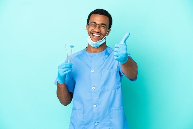 Afro-amerikaanse tandarts die gereedschap vasthoudt over geïsoleerde blauwe achtergrond met duimen omhoog omdat er iets goeds is gebeurd