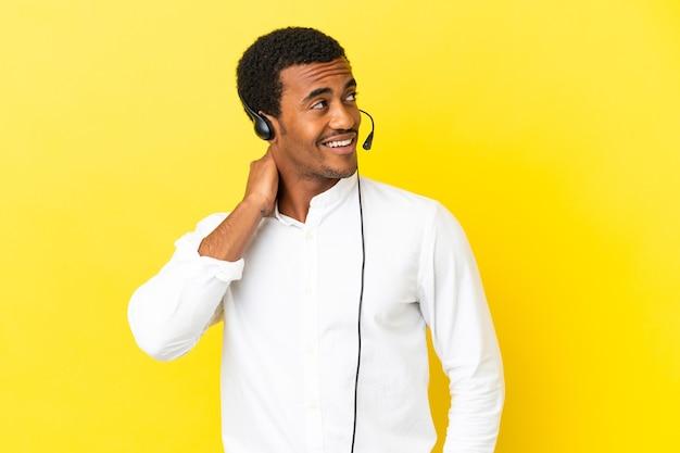 Afro-amerikaanse telemarketeer man aan het werk met een headset over geïsoleerde gele achtergrond denken een idee