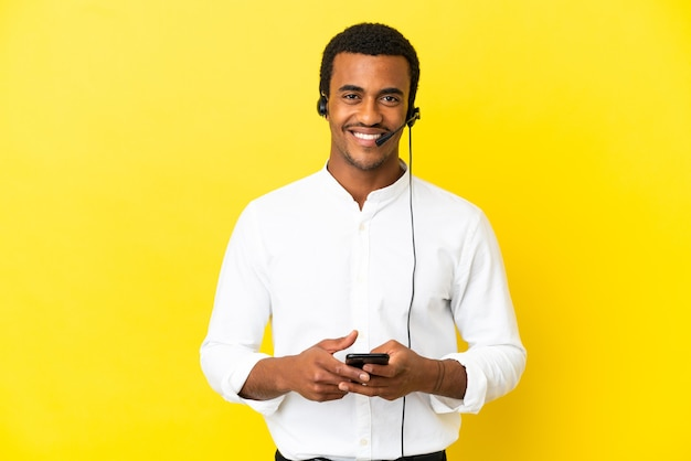 Afro-amerikaanse telemarketeer man aan het werk met een headset over geïsoleerde gele achtergrond die een bericht verzendt met de mobiel