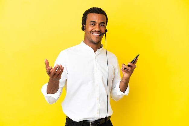 Afro-amerikaanse telemarketeer man aan het werk met een headset over geïsoleerde gele achtergrond die een gesprek voert met de mobiele telefoon met iemand