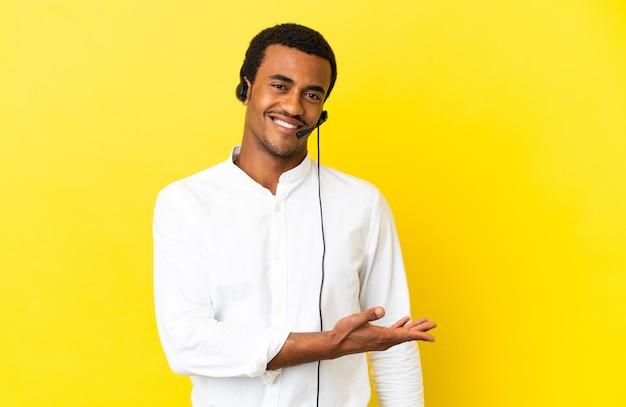 Afro-amerikaanse telemarketeer man aan het werk met een headset over geïsoleerde gele achtergrond die een idee presenteert terwijl hij glimlacht naar