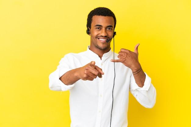 Afro-amerikaanse telemarketeer-man aan het werk met een headset over geïsoleerde gele achtergrond die een telefoongebaar maakt en naar voren wijst