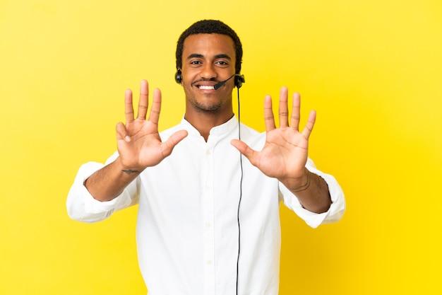 Afro-amerikaanse telemarketeer man aan het werk met een headset over geïsoleerde gele achtergrond die negen met vingers telt