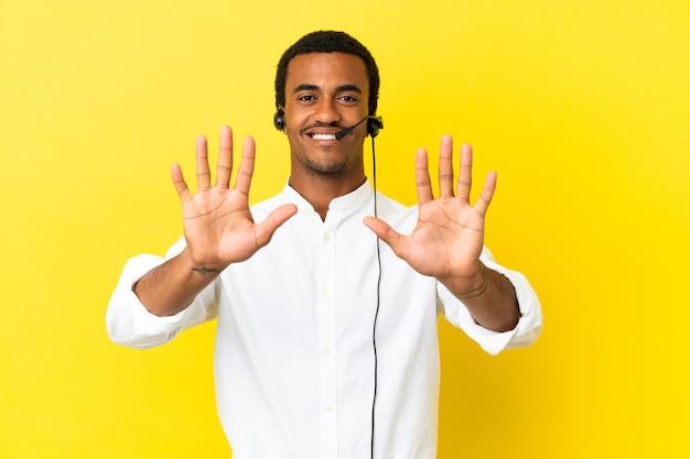 Afro-amerikaanse telemarketeer man aan het werk met een headset over geïsoleerde gele achtergrond die tien telt met vingers