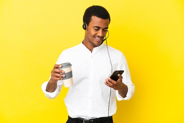 Afro-amerikaanse telemarketeer man aan het werk met een headset over geïsoleerde gele achtergrond met koffie om mee te nemen en een mobiel