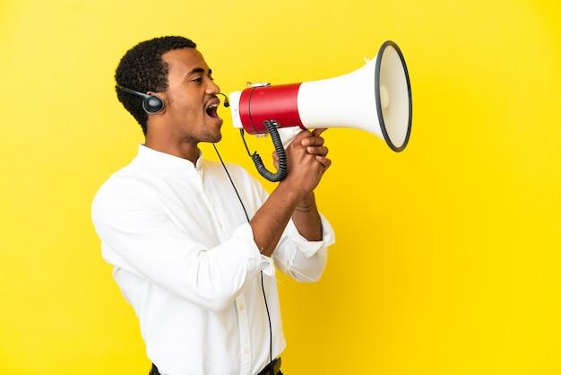 Afro-amerikaanse telemarketeer man aan het werk met een headset over geïsoleerde gele achtergrond schreeuwen door een megafoon